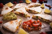 Quesadilla, mexican  tortilla wraps filled with cheese, meat and vegetables, cut in triangles poster
