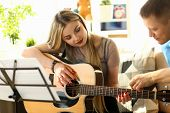 Musical Workshop At Home Couple Playing Guitar. Handsome Young Man Teaching His Girlfriend Performin poster
