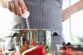 Culinary Chef Adding Saucepan White Sea Salt. Man In Apron Holding Spice Shaker In Hand. Male Finger poster