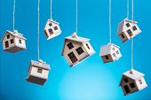 Miniature Houses Hanging By Strings Against Blue Background poster