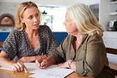 Female Friend Helping Senior Woman To Complete Last Will And Testament At Home poster