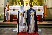 Bride And Groom During Wedding Ceremony In Church. Bride And Groom Preparing For Communion On Knees  poster