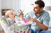 family, food, eating and people concept - happy father feeding little baby daughter sitting in highc poster