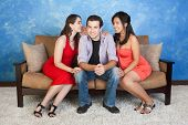 stock photo of threesome  - Two pretty women whisper and flirt with handsome man - JPG