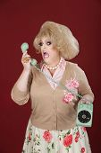 stock photo of cross-dresser  - Emotional queen screams at a rotary telephone - JPG