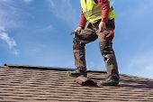 Unrecognizable Workman Standing On Tile Roof Of New Home Under Construction Against Blue Sky With He poster