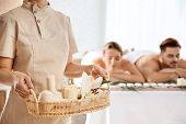 Massage Therapist With Spa Essentials And Young Couple In Wellness Center poster