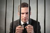 stock photo of delinquency  - Businessman in prison - JPG