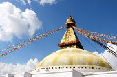Stupa With Buddha Eyes And Prayer Flags On Clear Blue Sky Background