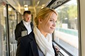 stock photo of commutator  - Woman in train looking pensive on window smiling travel commuting - JPG