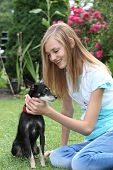 image of miniature pinscher  - Affectionate young teenager caressing her loyal pet a miniature pinscher dog as the two enjoy the summer day sitting on the lawn - JPG