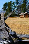 picture of log fence  - Wooden Log Fence Surrounding a Cabin in the Woods - JPG