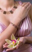 stock photo of partially clothed  - Women wearing evening dress holding a yellow and purple orchid flower in hands - JPG