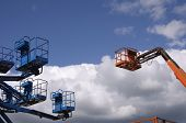image of cherry-picker  - cherry pickers extended into a blue sky - JPG