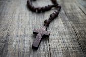 pic of rosary  - A rosary with beads on wooden textured background - JPG