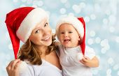 stock photo of christmas baby  - happy family mother and baby in red Christmas hats - JPG