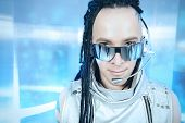 Eccentric futuristic man in silver costume and headset. Innovations and high technology. Rock artist