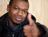 stock photo of afrikaner  - Black guy showing thumbs up - JPG