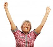 portrait of a cheerful senior woman gesturing victory over a white background