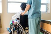 Midsection of nurse holding patient's wheelchair's handle by window in hospital