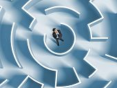 stock photo of maze  - Top view of successful businessman standing in center of labyrinth - JPG