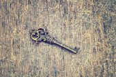 stock photo of skeleton key  - Old ornate skeleton key on rough wood background with retro filter effect - JPG