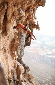Female rock climber resting while hanging on rope