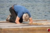 stock photo of bent over  - A senior man bent over working on repairs on an aging wooden dock or raft with the lake in the background - JPG