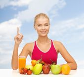 fitness, diet and food concept - young woman with organic food or fruits holding finger up