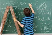 image of mathematics  - Highly intelligent little boy in the classroom standing on a stepladder to reach a complex mathematical problem on the blackboard that he is busy solving