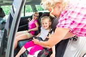 stock photo of seatbelt  - Mother buckling up on child in car safety seat  - JPG