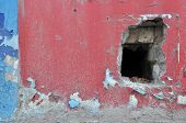 foto of neglect  - Background of neglected wall with a hole and layers of old paint  - JPG