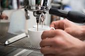 stock photo of dispenser  - Hands of professional barista holding two white cups on the grating of coffee machine looking how coffee pouring into them - JPG
