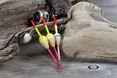 pic of driftwood  - Closeup horizontal image of fishing objects consisting of floats reel single lure all resting against aged driftwood