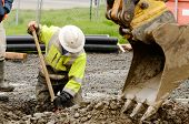 stock photo of excavator  - Worker using a small tracked excavator to dig a hole to fix a water leak at a large commercial housing development in Oregon - JPG