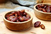stock photo of fruit bowl  - Fruits dates in wooden bowl closeup on table - JPG