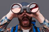 picture of binoculars  - Surprised young bearded man carrying backpack and looking through binoculars while standing against grey background - JPG