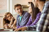 stock photo of classmates  - Smiling friends students talking together at school - JPG