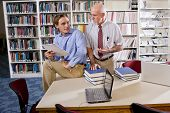 College Professor With Student Talking In Library