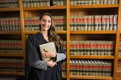 picture of laws-of-attraction  - Pretty lawyer looking at camera in the law library at the university - JPG