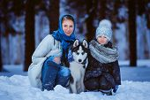 foto of puppies mother dog  - mother and young daughter walking with husky dog winter time - JPG