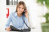 picture of file folders  - Young business woman phoning in office sitting at an office desk with one hand holding the phone and in another folder - JPG
