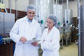 image of scientist  - Scientist speaking to his colleague holding clipboard in the factory - JPG