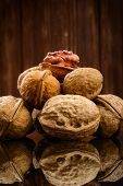 picture of walnut  - Walnut kernels and whole walnuts on rustic old wooden background
