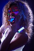 stock photo of uv-light  - Image of amusing visage model posing in UV light - JPG