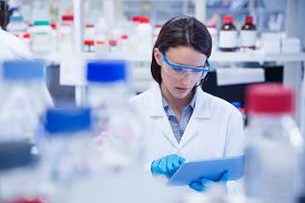 stock photo of chemistry technician  - Chemist wearing safety glasses and using tablet pc in lab - JPG