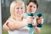 foto of personal assistant  - Female training with dumbbells assisted by physiotherapist - JPG