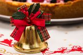 picture of cheesecake  - Golden bell with green and red ribbons on top at a dinner table on a tablecloth with reindeers with an out of focus cheesecake on the background - JPG