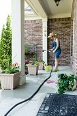 picture of sprinkler  - Woman gardener standing watering newly potted decorative spring plants arranged in flowerpots along an open - JPG
