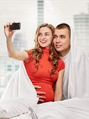 picture of two women taking cell phone  - A pregnant woman and her husband are photographing themselves on the cell phone at home - JPG